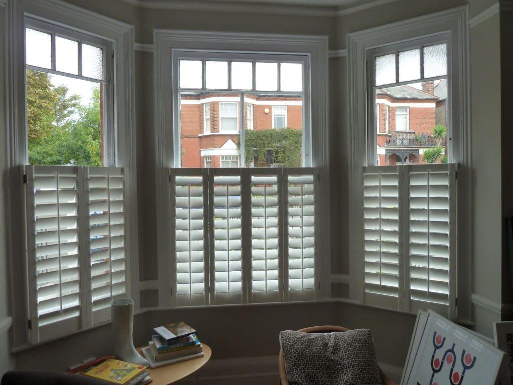 white wooden shutters for bay windows